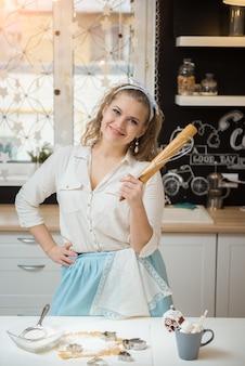 Sorridente giovane chef con accessori per cucinare