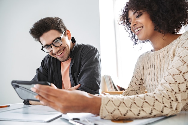 Giovani colleghi sorridenti che usano lo smartphone insieme mentre sono seduti al tavolo in ufficio