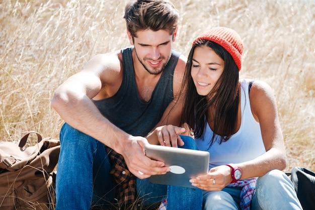 Sorridente giovane coppia in viaggio in campeggio utilizzando la tavoletta digitale all'esterno