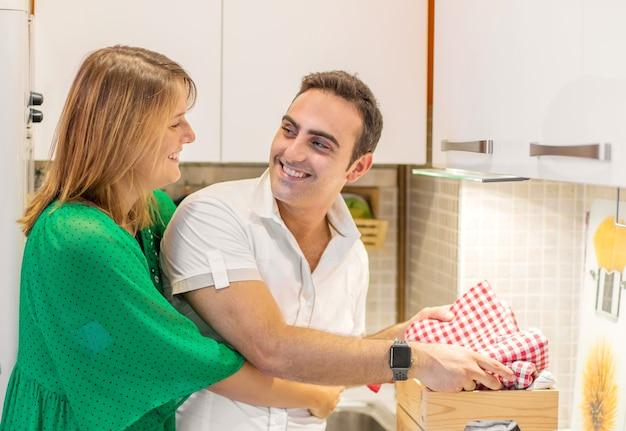 Sorridente giovane coppia che cucina cibo in cucina