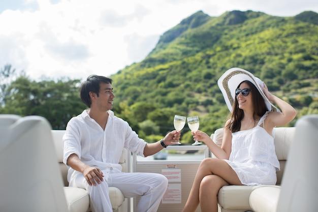 Giovani coppie sorridenti che tengono i vetri con champagne e che guardano l'un l'altro mentre sedendosi sul bordo dello yacht