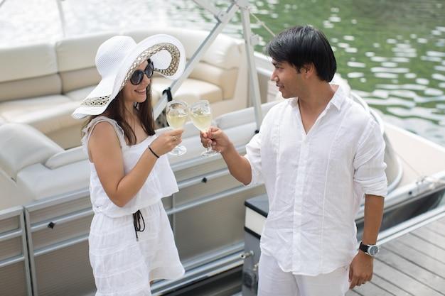 Giovani coppie sorridenti che tengono i vetri con champagne e che esaminano