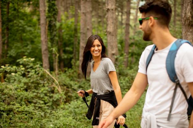 Sorridente giovane coppia che cammina con gli zaini nella foresta in una giornata estiva