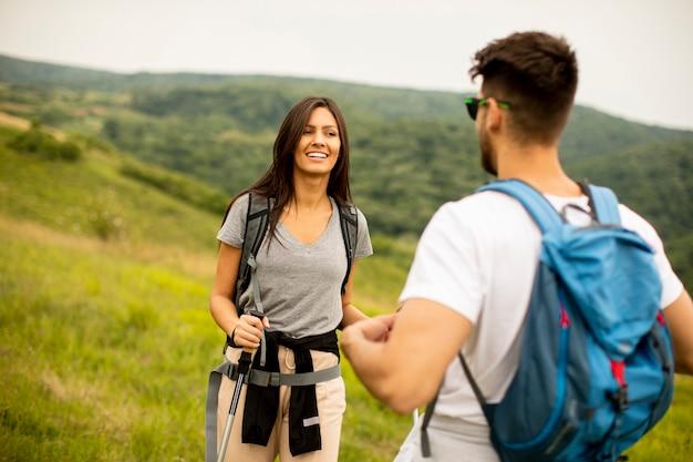 Giovani coppie sorridenti che camminano con gli zaini su verdi colline in una giornata estiva