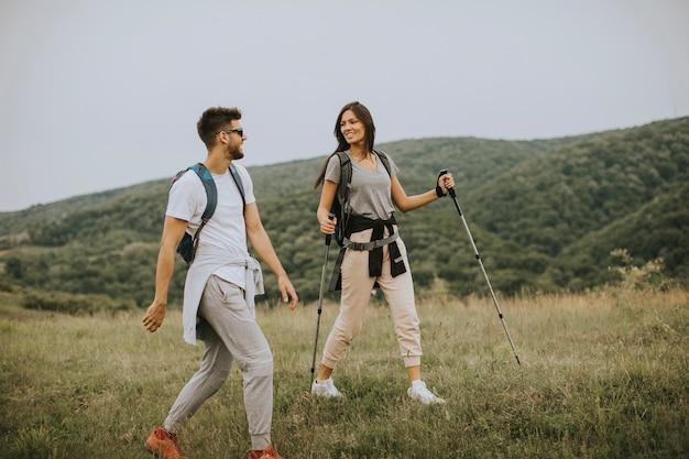 Sorridente giovane coppia che cammina con gli zaini su verdi colline in un giorno d'estate