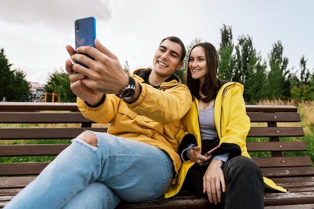 La giovane coppia sorridente in giacche gialle prende un selfie, foto su uno smartphone