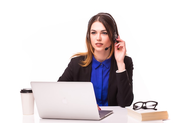 Una giovane ragazza sorridente del servizio clienti con un auricolare sul posto di lavoro