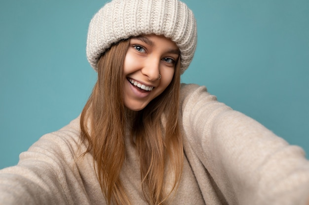 Sorridente giovane donna bionda scura in piedi isolato su sfondo colorato muro indossando abiti alla moda di tutti i giorni guardando la telecamera che mostra le emozioni del viso.
