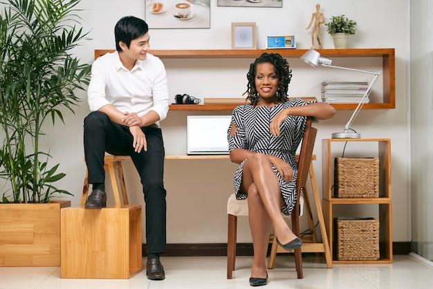 Sorridente giovane uomo d'affari asiatico lieto guardando il suo riuscito collega femminile sicuro