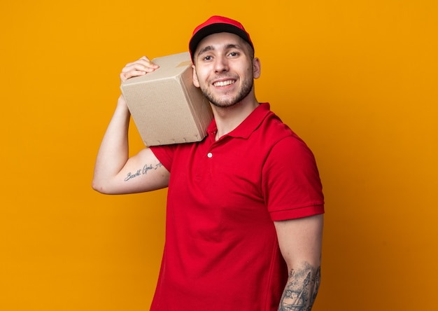Sorridente giovane fattorino che indossa l'uniforme con il cappuccio che tiene la scatola sulla spalla