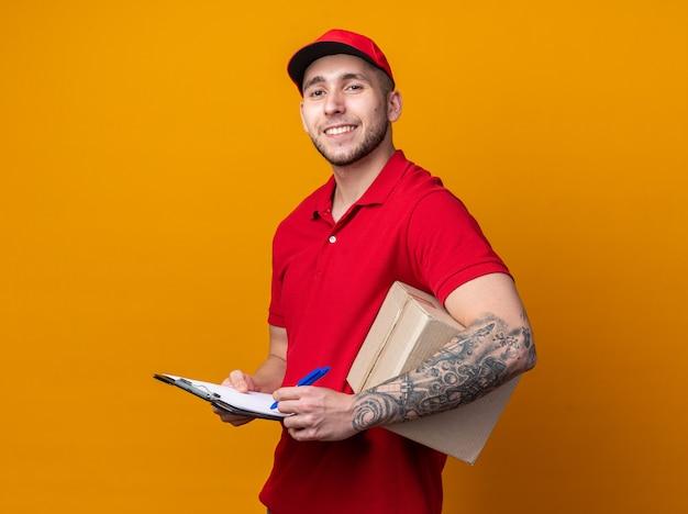 Sorridente giovane fattorino che indossa l'uniforme con il cappuccio che tiene la scatola con gli appunti