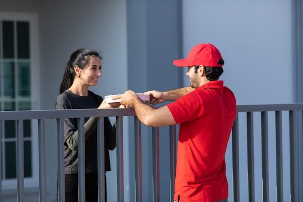 Il giovane fattorino sorridente in uniforme rossa che tiene una scatola dà al cliente della bella donna davanti alla casa.
