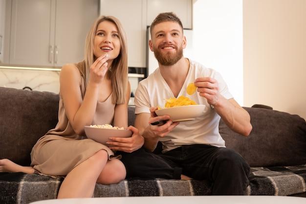 Sorridente giovane coppia europea seduta sul divano e guardare la tv o un film. ragazzo e ragazza che mangiano patatine e popcorn. tempo libero e riposo a casa. concetto di godersi il tempo insieme. interno del monolocale