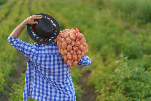 Sorridente giovane agricoltore che tiene un sacco di patate fresche sul campo di patate verdi