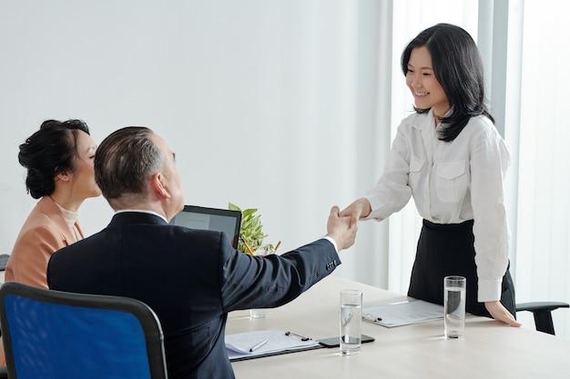 Sorridente giovane candidata che stringe la mano al responsabile delle risorse umane e al ceo dell'azienda prima del colloquio di lavoro