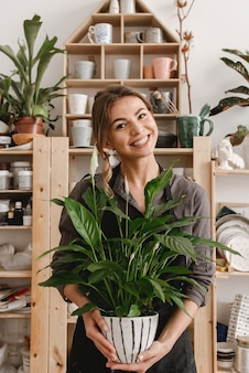 Sorridente giovane femmina ceramista azienda pianta.