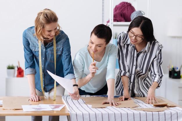 Sorridente giovane designer femminile che mostra uno schizzo di abbigliamento ai suoi colleghi mentre lo guardano con interesse, avendo distratto dai modelli di tracciamento