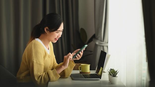 Una giovane imprenditrice sorridente seduto a un tavolo nel suo ufficio a casa