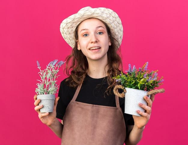Sorridente giovane giardiniere femminile che indossa cappello da giardinaggio con fiori in vasi da fiori isolati su parete rosa