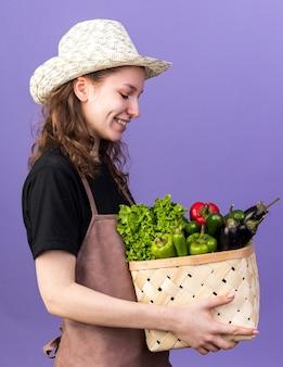 Sorridente giovane giardiniere femminile che indossa cappello da giardinaggio tenendo e guardando cesto di verdure isolato su parete blu
