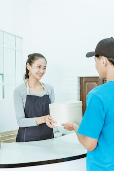 Sorridente giovane negoziante di sesso femminile che riceve un pacchetto dal corriere