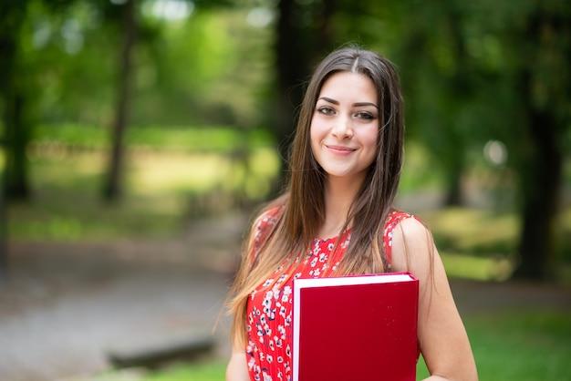 Sorridente giovane studentessa che cammina in un parco