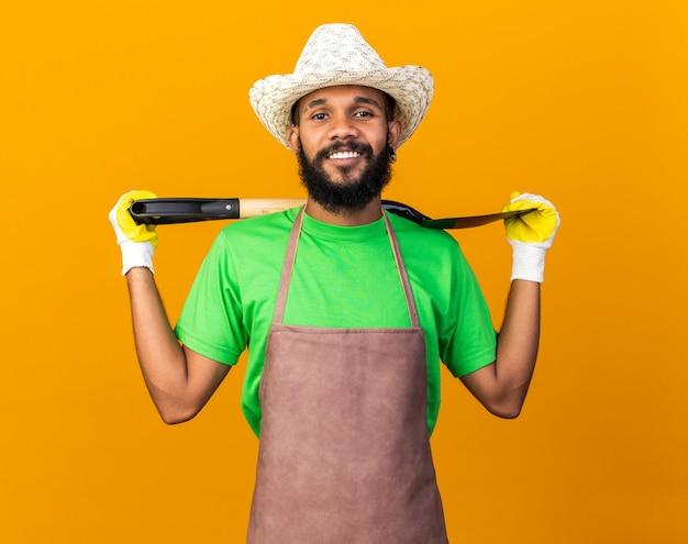 Sorridente giovane giardiniere afro-americano che indossa cappello e guanti da giardinaggio che tengono la vanga sulla spalla isolata sul muro arancione