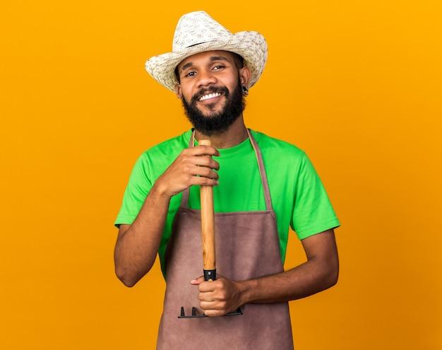 Sorridente giovane giardiniere afro-americano che indossa un cappello da giardinaggio che tiene rastrello isolato sul muro arancione