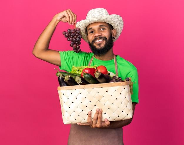 Sorridente giovane giardiniere afro-americano che indossa cappello da giardinaggio con cesto di verdure con grappe