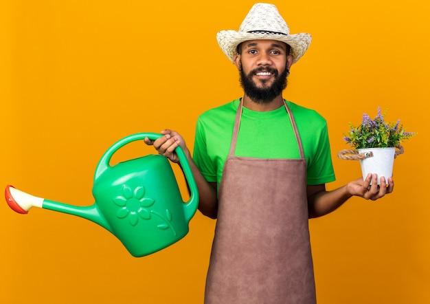 Sorridente giovane giardiniere afro-americano che indossa un cappello da giardinaggio che tiene in mano un annaffiatoio con un fiore in un vaso di fiori