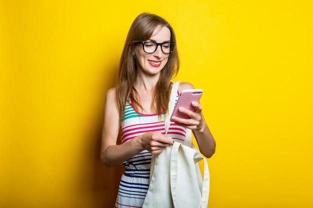 Ragazza sorridente con gli occhiali guarda il telefono, con un sacchetto di lino sulla spalla su uno sfondo giallo.