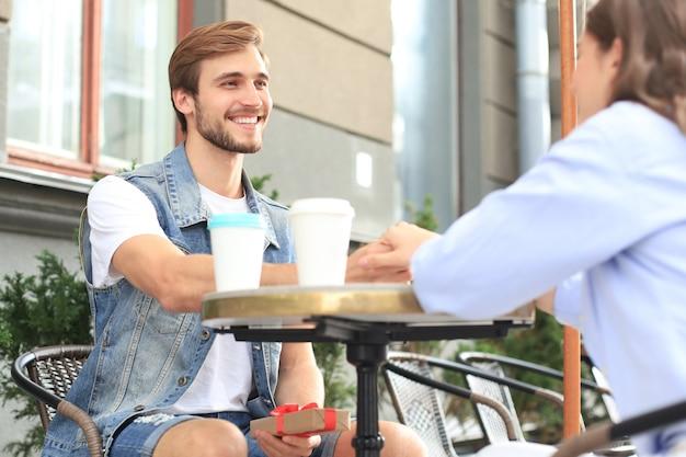 Sorridente ragazza che ha un appuntamento con il suo ragazzo al bar, uomo che tiene la scatola presente.