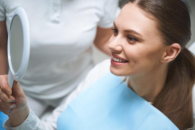 La ragazza sorridente si guarda allo specchio per valutare il lavoro del dentista e godersi il risultato con uno specialista