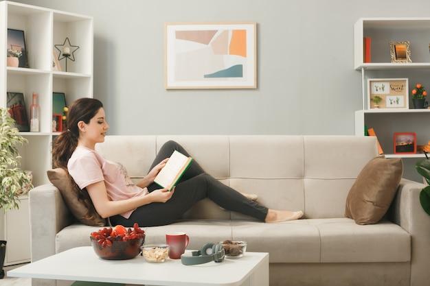 Sorridente ragazza sdraiata sul divano dietro il tavolino da caffè leggendo un libro in soggiorno