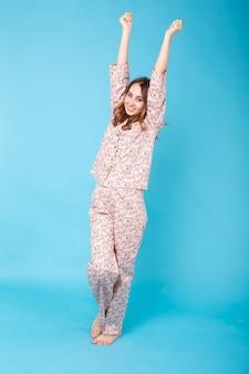 Sorridente ragazza in pigiama home indossare in posa mentre si riposa a casa isolato su sfondo blu