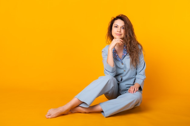 Sorridente ragazza in pigiama casa indossare in posa mentre riposa a casa isolato sulla parete gialla