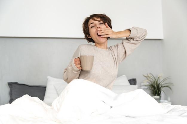 Sorridente ragazza giovane rilassante a letto la mattina, tenendo la tazza di caffè