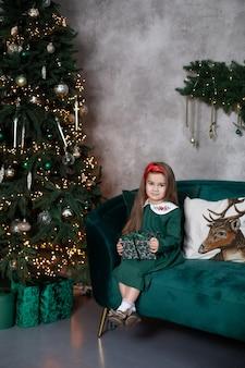 La ragazza sorridente si siede con il regalo sul sofà dall'albero di natale nell'accogliente soggiorno