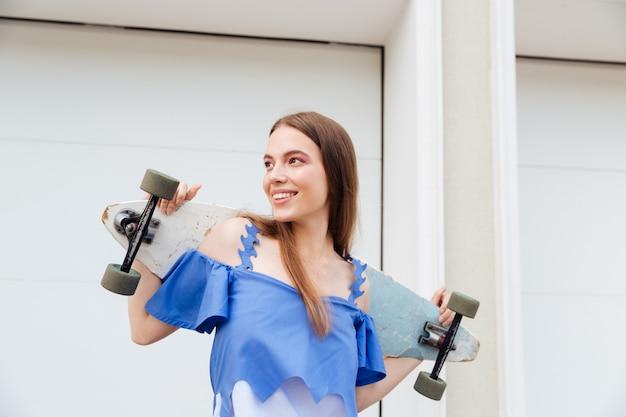 Sorridente ragazza giovane in piedi con lo skateboard all'aperto su sfondo bianco muro