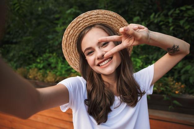 Ragazza sorridente che prende un selfie con la mano outsretched al parco all'aperto, mostrando la pace