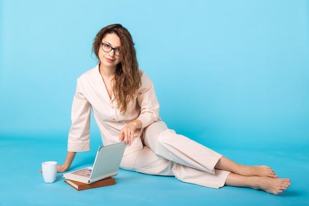 Sorridente ragazza con libri in pigiama casa indossare in posa mentre si riposa a casa isolato su sfondo blu ritratto in studio. rilassati il concetto di stile di vita di buon umore.