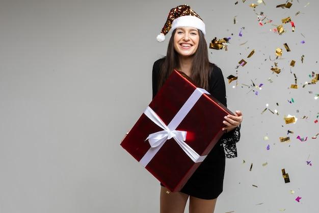 Ragazza sorridente con un grande regalo festivo che punta a mano su uno spazio vuoto con coriandoli festivi su ...