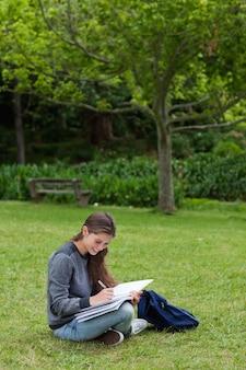 Scrittura sorridente della ragazza sul suo taccuino mentre sedendosi sull'erba