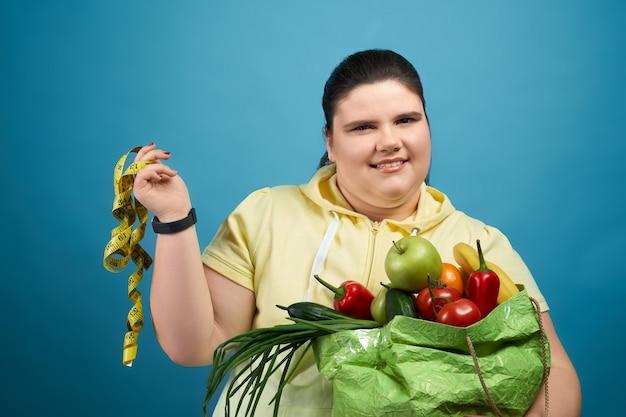 Ragazza sorridente in maglione giallo che guarda l'obbiettivo e mantenendo il pacchetto con frutta e verdura da un lato e misurando il teape sull'altro. concetto di scelta di cibo sano per un bel corpo.