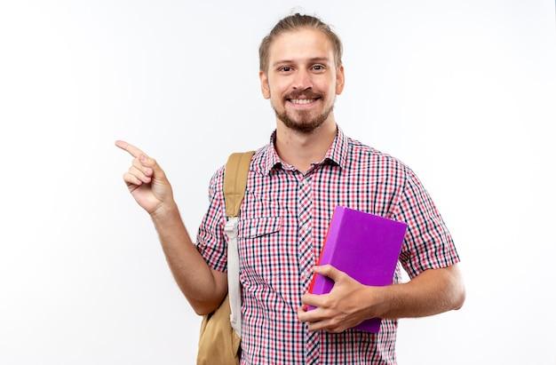 Sorridente giovane studente che indossa uno zaino con in mano i punti di libri a lato