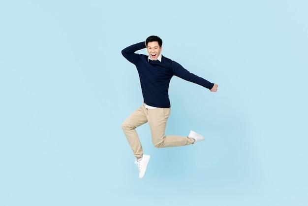 Giovane uomo asiatico bello sorridente che salta sulla parete blu-chiaro