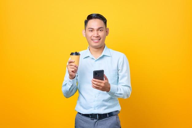 Sorridente giovane uomo d'affari bello che tiene smartphone e tazza di caffè su sfondo giallo