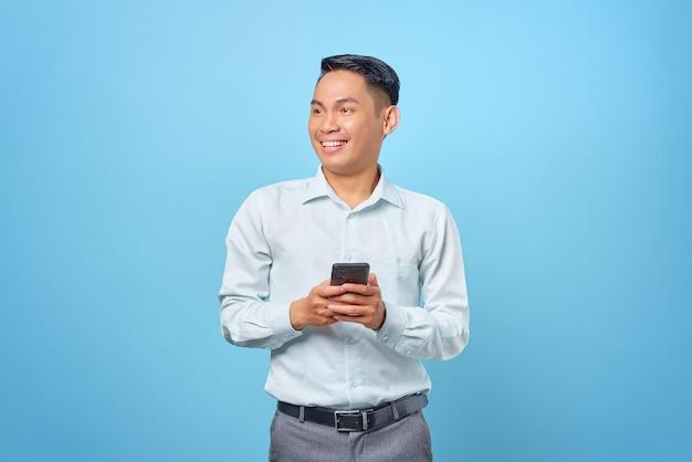 Sorridente giovane uomo d'affari bello che tiene smartphone e guarda da parte su sfondo blu