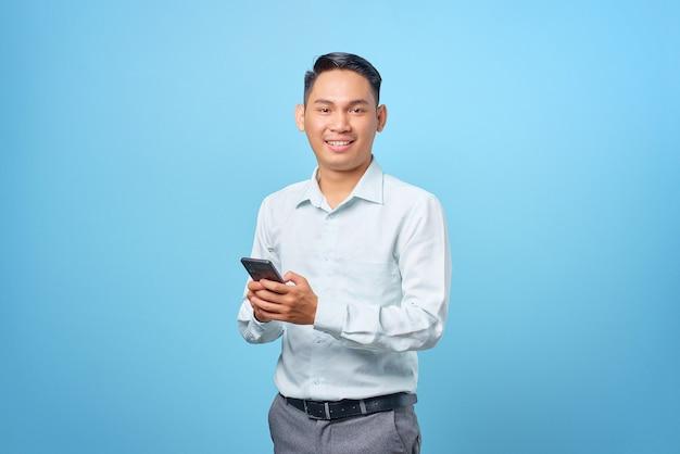 Sorridente giovane uomo d'affari bello che tiene smartphone e guarda la telecamera su sfondo blu