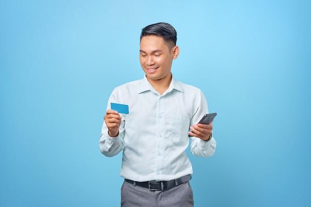 Sorridente giovane uomo d'affari bello che utilizza smartphone e tiene in mano una carta di credito su sfondo blu